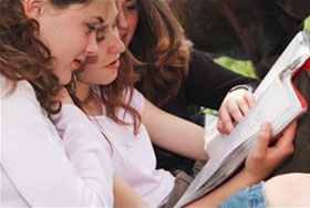 Female students reading a document